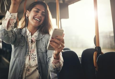 Woman smiling at phone on bus